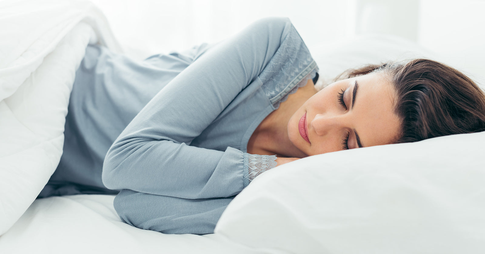 Women with blue top on asleep in bed on her side