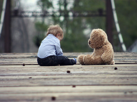 Little boy playing with his soft toy, teddy bear