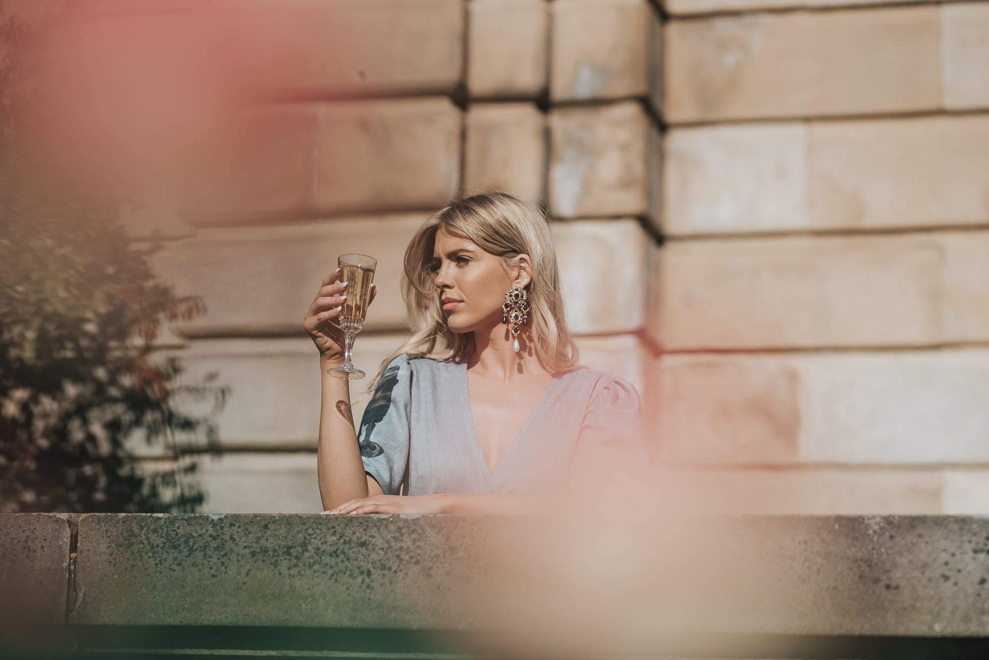 Image shows the Alice Dress, the perfect wedding guest outfit. Calla poses with champagne in hand over a romantic stone balcony. Shining in the sun she has her arm placed in the cool stone and you can clearly see the elegant blue wrap front of the dress.