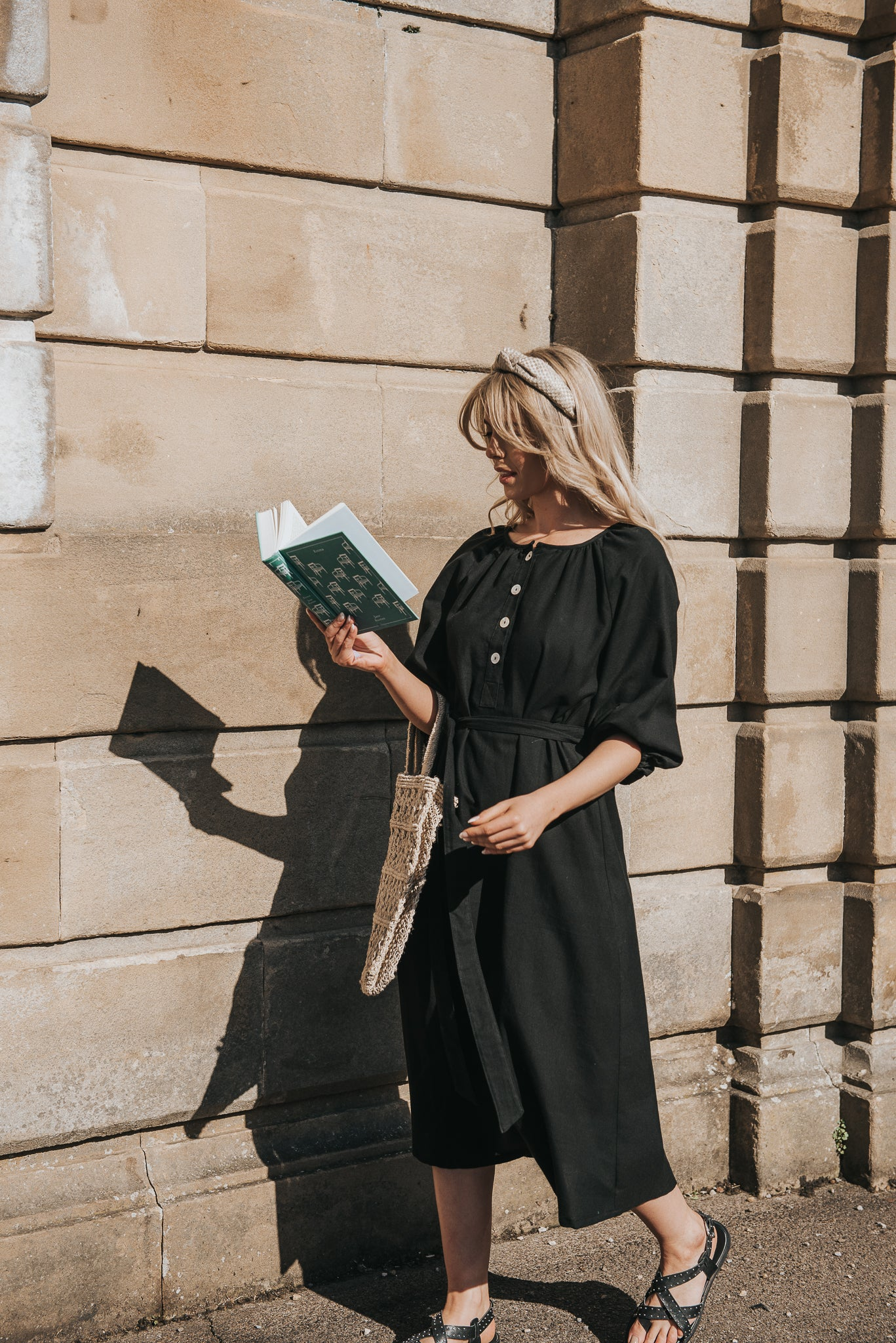 Walking with novel in hand in the sunshine, Calla wears the black Georgiana dress in Midi Length. Featuring raglan puff sleeve and elegant scoop round neckline.