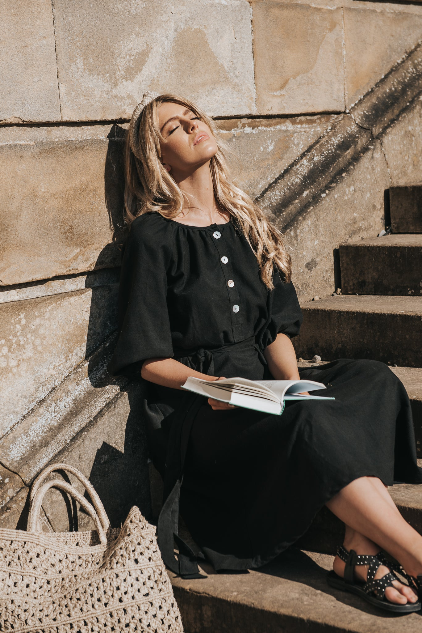 An elegant sun dress, with round neckline and shell button placket. Midi length with raglan puff sleeves in black hand woven cotton. Calla sits in countryside style reading Jane Austin, Emma. Breast feeding friendly. Bump and maternity friendly