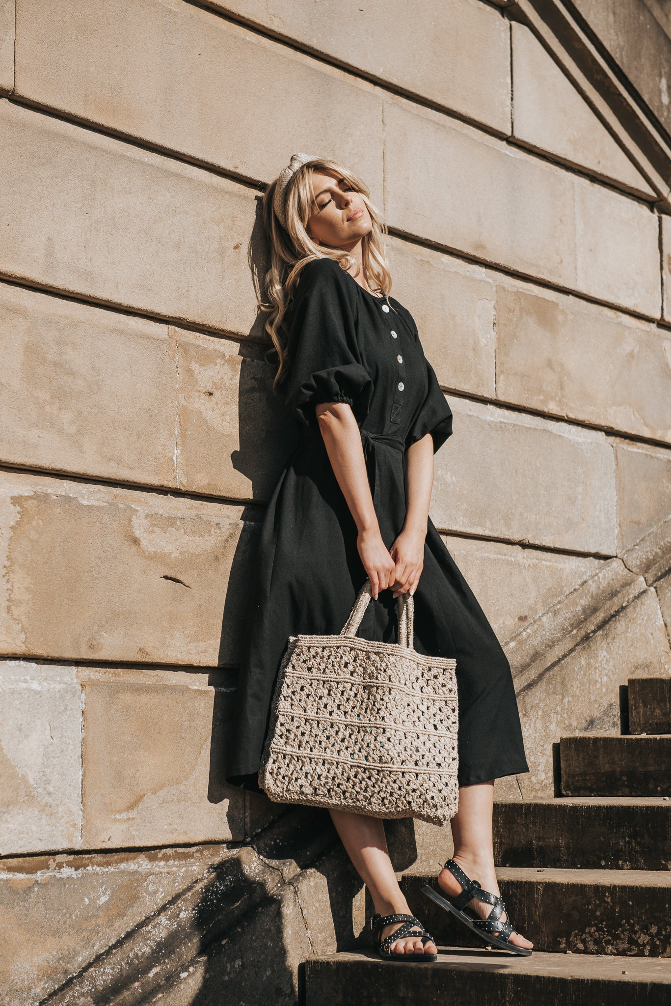 Standing in the sun, wearing the Georgiana Midi dress in black handwoven cotton. Styled with a natural woven headband and handwoven Maison Bengal Jute tote bag and black leather gladiator sandals.