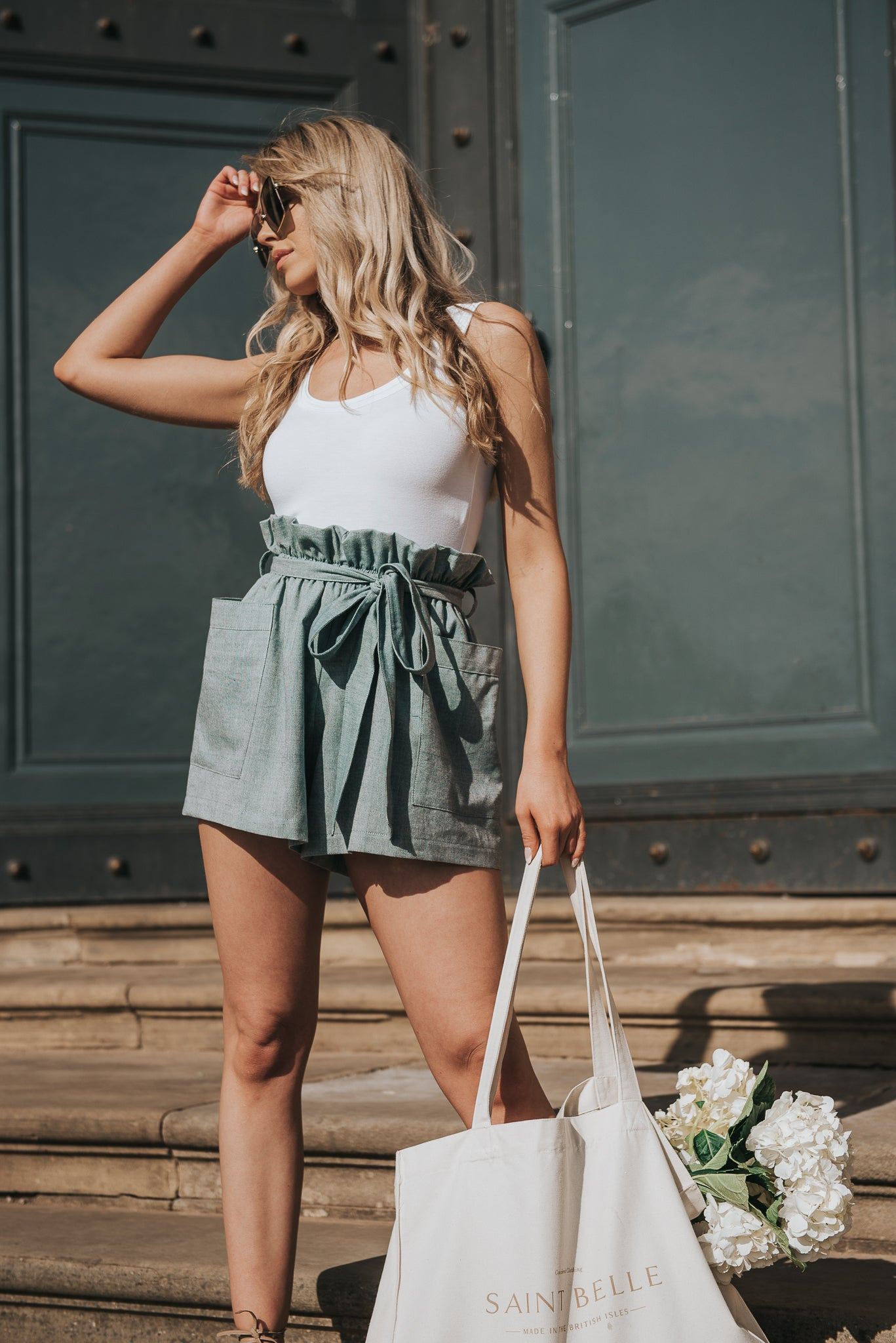 Summer shorts, standing on stone steps. Slightly oversized with an elasticated paperbag waistline. Features deep square patch pockets. Practical and stylish