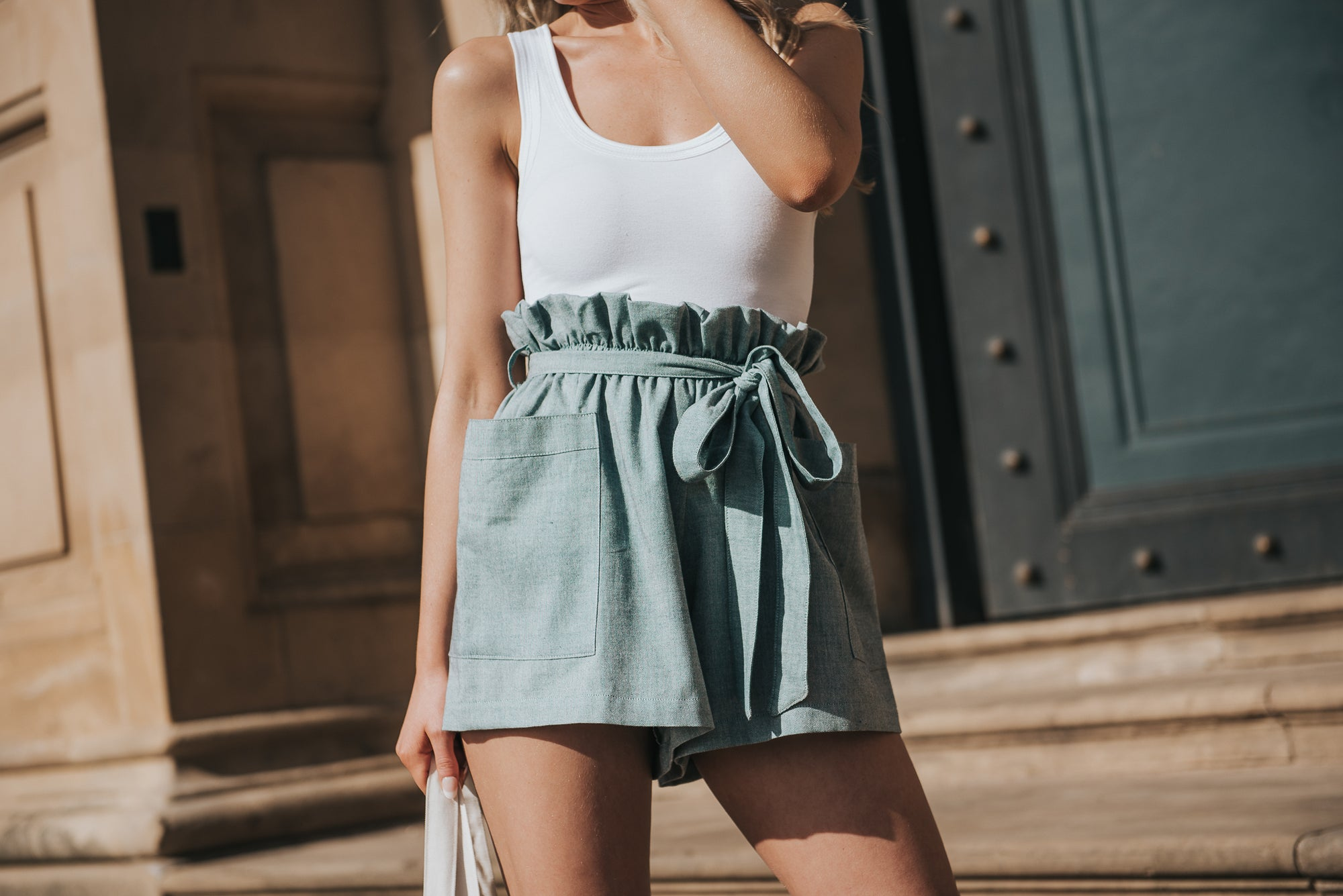 Standing on stone steps in front of large parisian style blue door. The Eva shorts, loose fitting short with elasticated paper bag waist in a soft handwoven cotton fabric. The shorts have large pockets. Styled with a scoop neck white cotton cami vest top