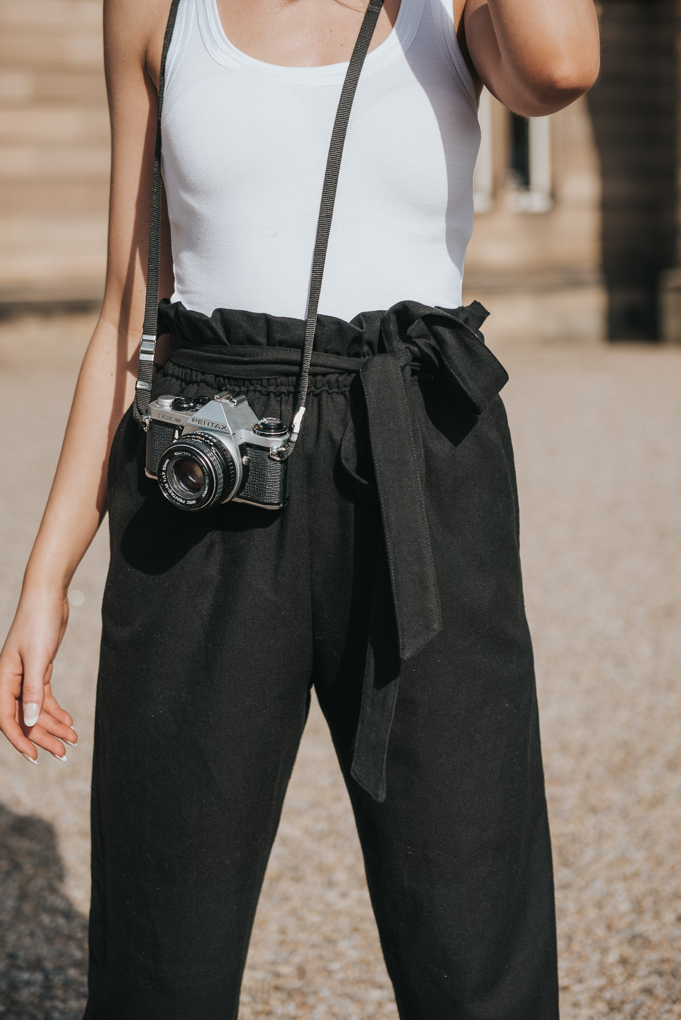 A comfortable cotton trouser, with elasticated paperbag waistline. Can be tied with fabric belt tie. Soft and loose fitting, style up or down. Calla wears with white round neck cami and has a camera worn across her body