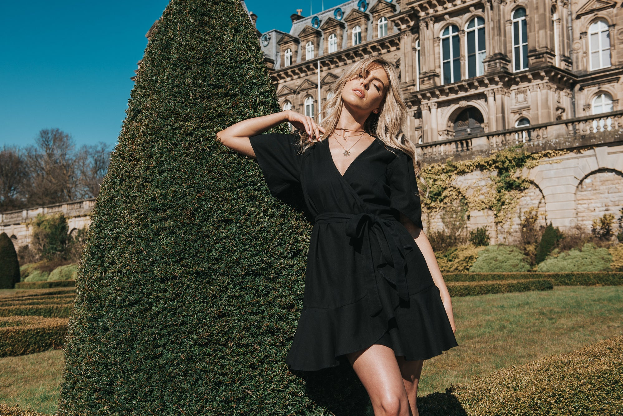 Standing in the grounds of the Bowes Museum. The Isabella mini wrap dress is stylish and sustainable. Fabricated in our handwoven black cotton, all natural fibres of which 30% is from a recycled source. Aiding a more circular textile economy