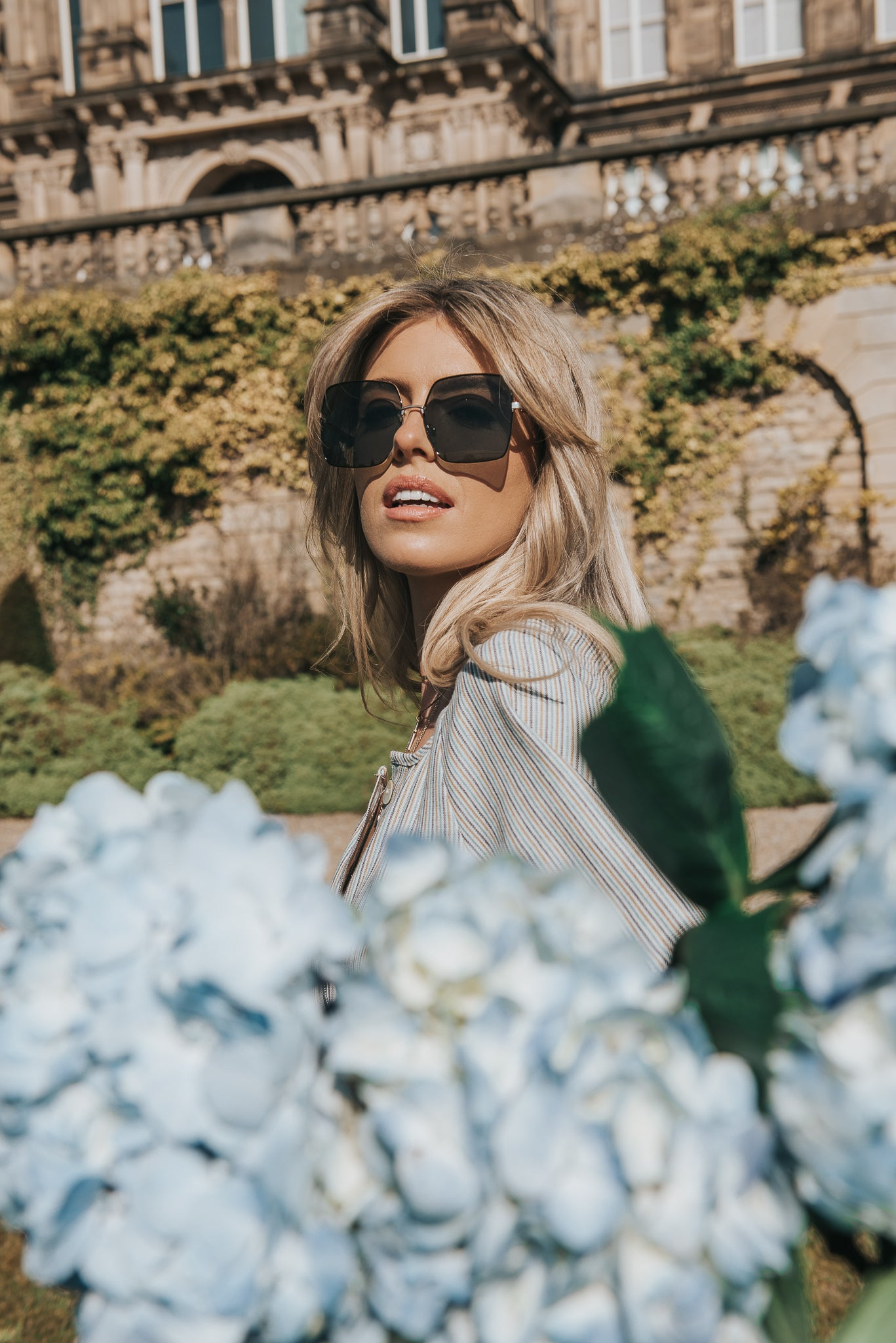 Peering through the blue hydrangea in true french country style Callas blonde hair shines in the sun, she wears large sunglasses and the Bowes Museum and gardens soaks up the sun in the background