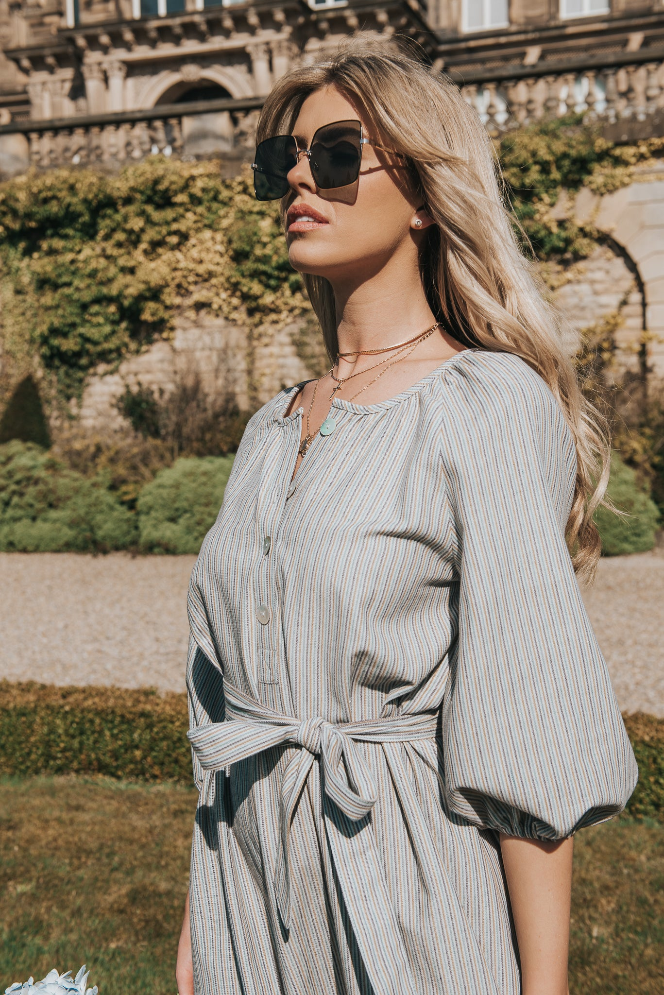 Standing towards the sunlight. The Georgiana dress in Meadow Stripe is shown. The natural shell buttons glint in the sun and the puff sleeve oversized style looks romantic, finished with a belt tie at the waist. Bump and Maternity, Breast feeding friendly