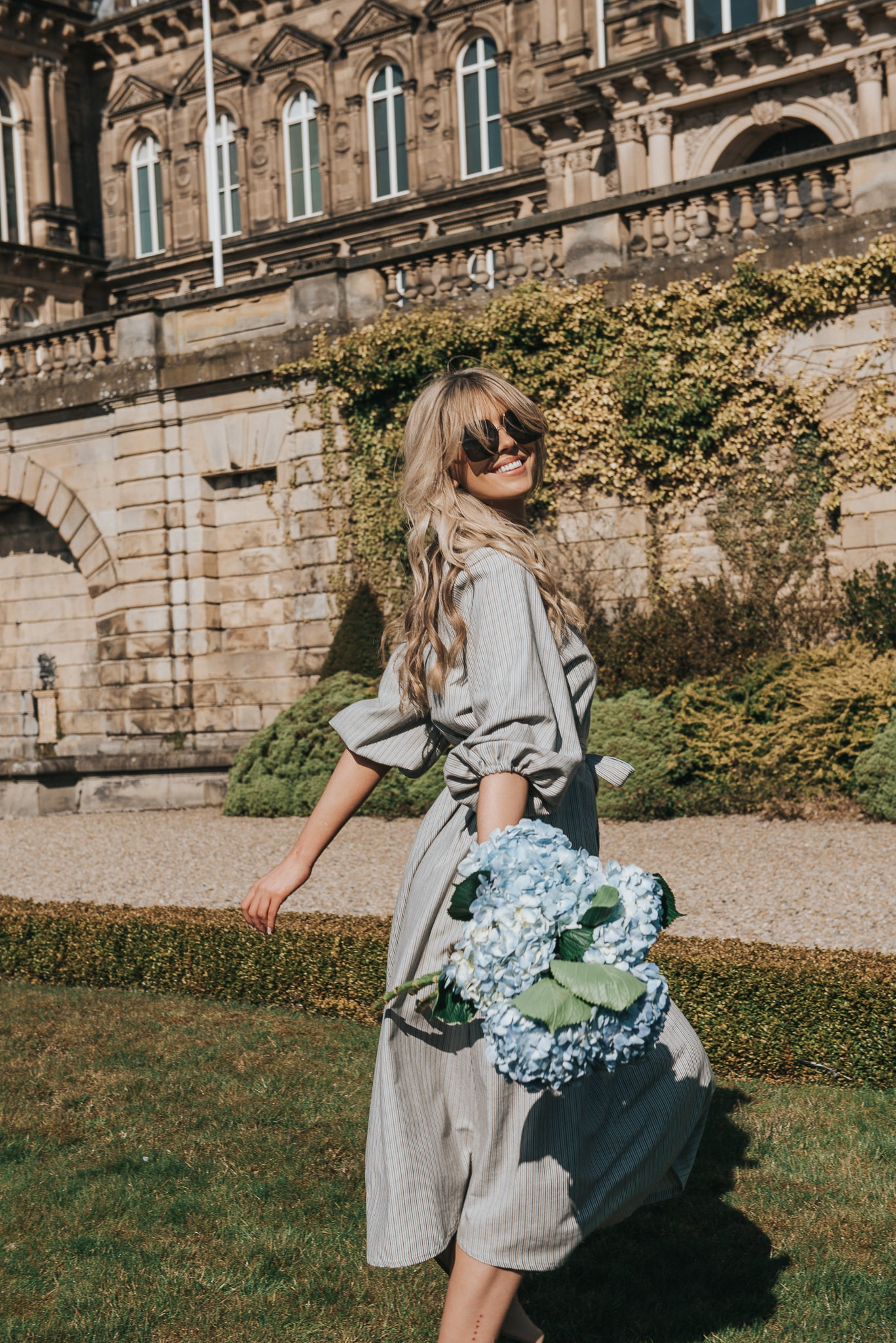 Dancing in the sunshine with fresh flowers. The Georgiana dress is the perfect style to explore french chateau grounds, in this image you can see how the detail in the oversized puff sleeve silhoutette