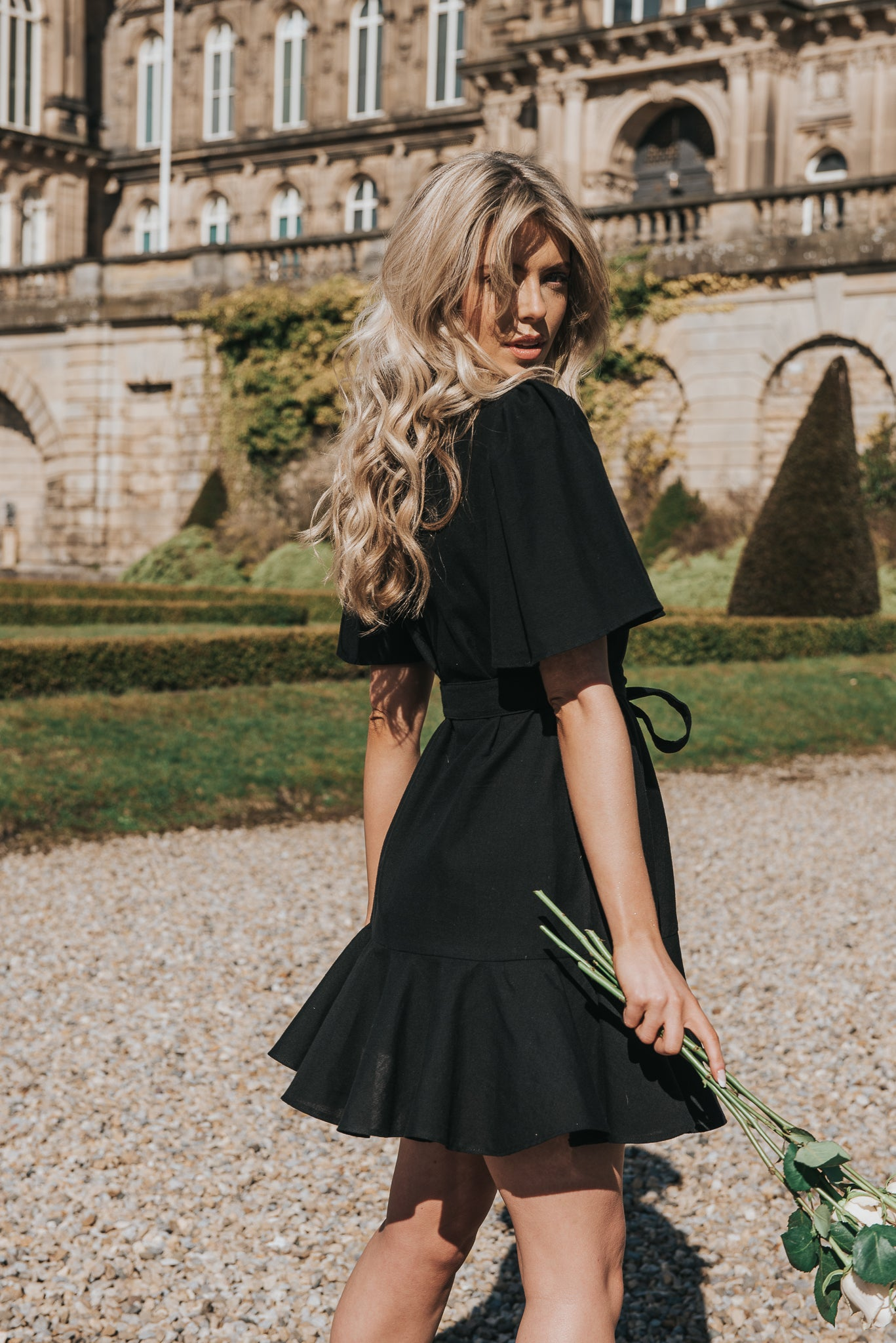 Our bestselling style, the Isabella dress in black hand loomed cotton. Style and sustainability! The perfect wrap mini dress with hem frill and soft cotton belt time. Calla holds stem roses and gazes into the camera