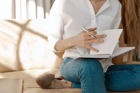 Woman Writing Down Affirmations In A Notebook