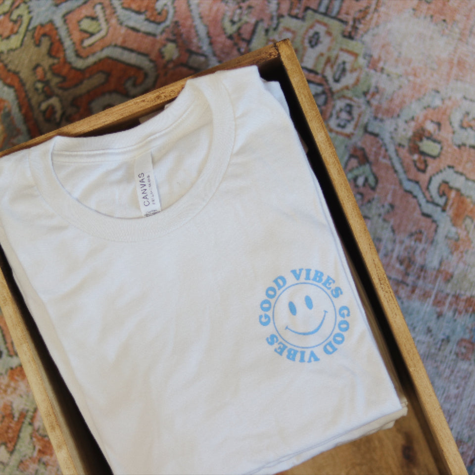 Good Vibes t-shirt in wooden crate on colorful oriental rug.