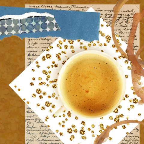 White mug of coffee on white table with gold confetti