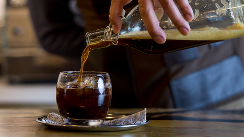 Pouring cold brew coffee from a glass bottle into a small glass with ice