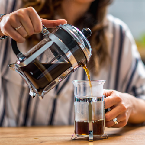 Woman in striped shirt pouring coffee from a French press into a glass mug