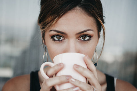 Latinx woman sipping coffee from a white mug