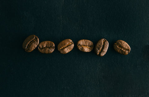 six coffee beans on a black background. Photo by Max D. Photography.