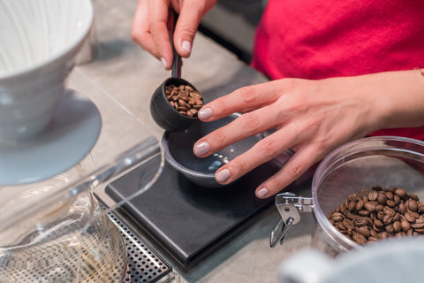 Weighing coffee beans on a kitchen scale. Photo by Victor Muñoz.