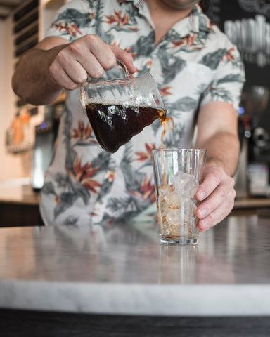 Man in floral shirt pouring coffee over ice in a clear glass. Photo by Wade Austin Ellis.