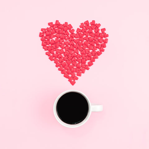 red candies forming a heart shape on a flat pink surface above a white mug of black coffee