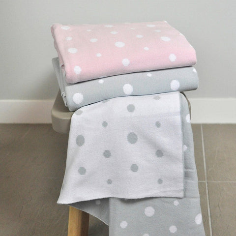 Cotton Bassinet Blanket in soft pink and white spots, folded stack.