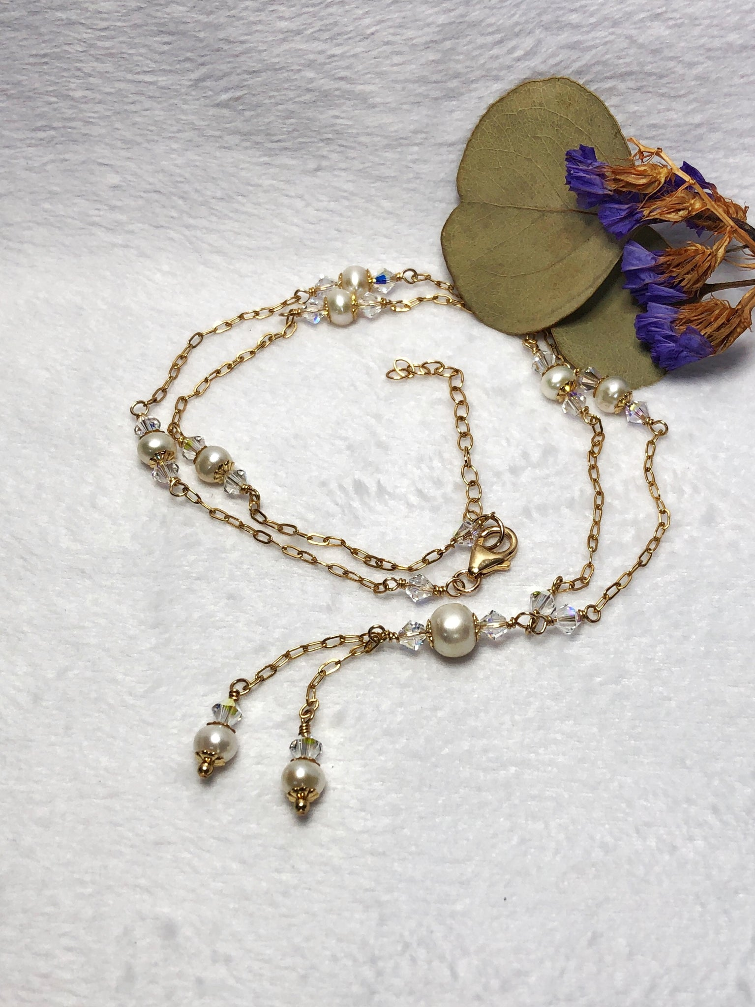 Freshwater pearl Swarovski crystal gold filled necklace laying flat on a white background