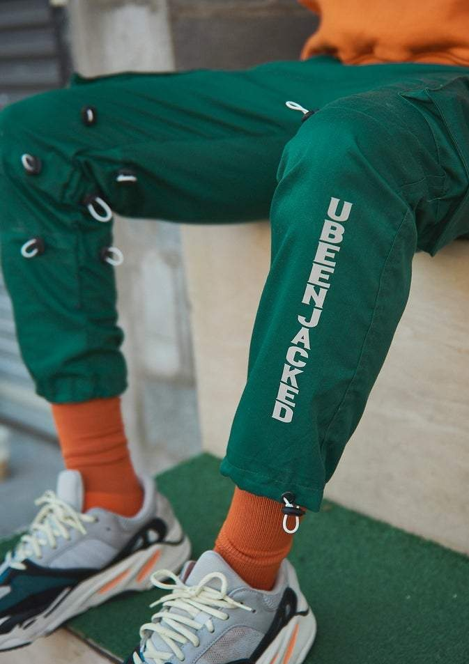 Close up UBEENJACKED reflective print on green cargo pants