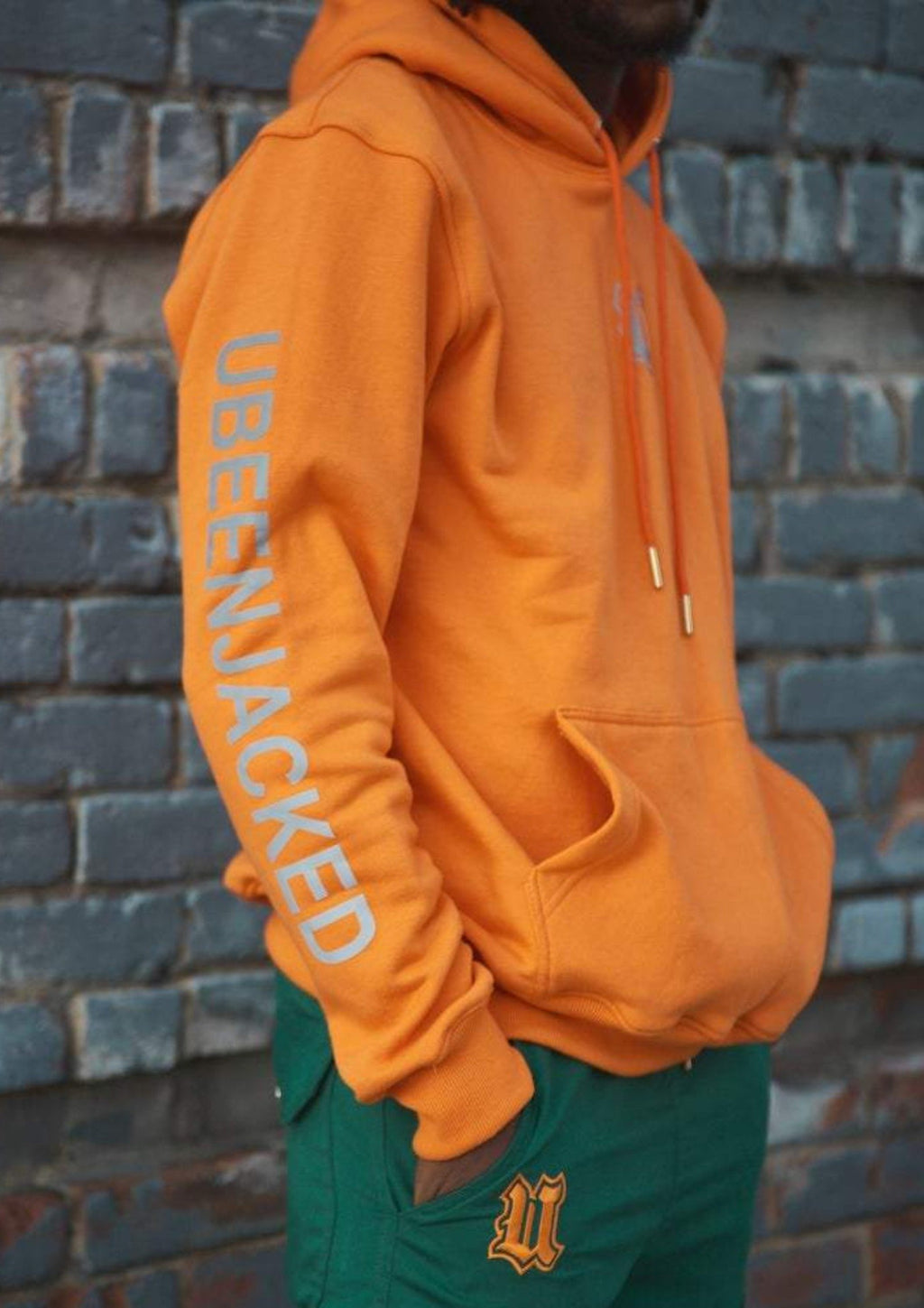 Side View Orange UBJ hoodie with reflective print on the arm