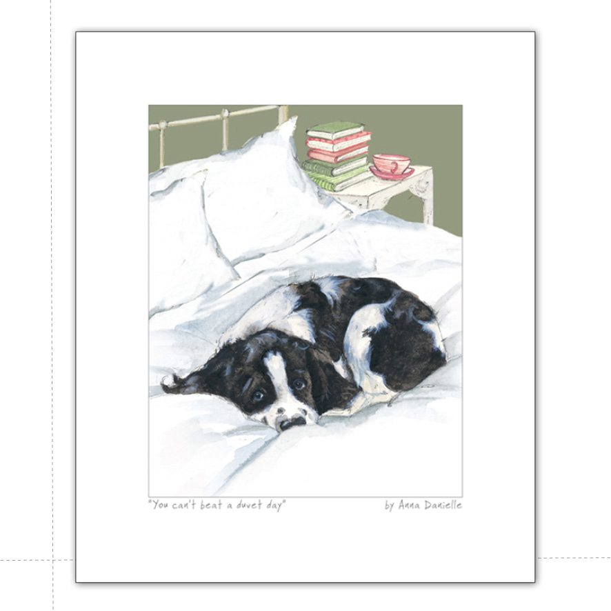 art print featuring black and white spaniel curled in bed and caption 'you cant beat a duvet day'
