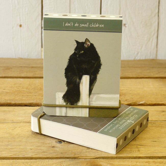 Notebook featuring long haired black cat stacked on a wooden bench