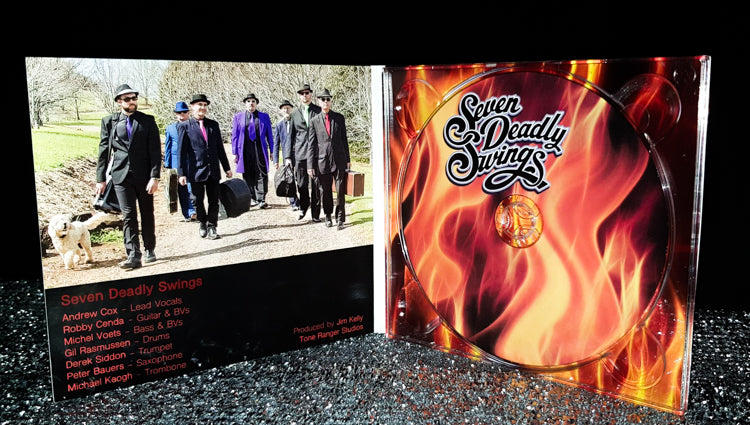 seven deadly swings album cover, artwork flames as background for title, insert showing band members carrying instrument cases along a road