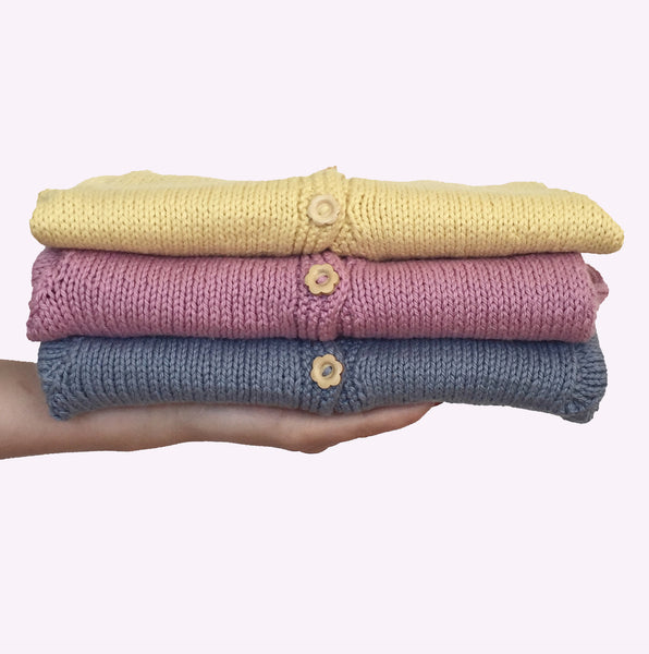 Three cotton cardigans in yellow, pink and blue with wooden daisy buttons