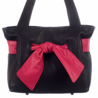 Black leather handbag with brightly coloured bow