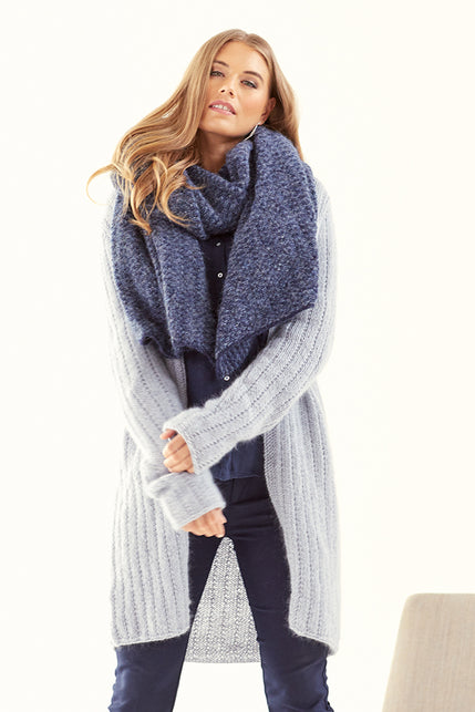 woman wearing a long knit light grey cardigan with eyelet vertical stripes and a thick textured blue knit wrap