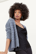 woman wearing a blue-grey knit cardigan with eyelet stripes