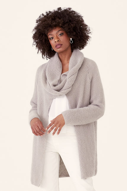 woman wearing a textured knit cardigan in light grey with a cowl-wrap neck