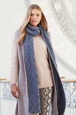 woman wearing a lilac long knit vest over a pink knit sweater with a cabled deep lavender knit long scarf