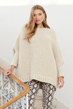 woman wearing an oversized textured knit sweater in cream