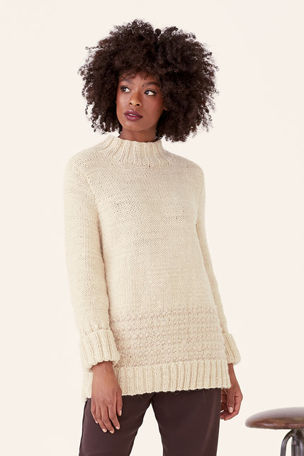 woman wearing a cream tube-neck knit sweater with textured stripes at the bottom of the body