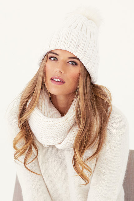 woman wearing a white knit hat, sweater, and cowl