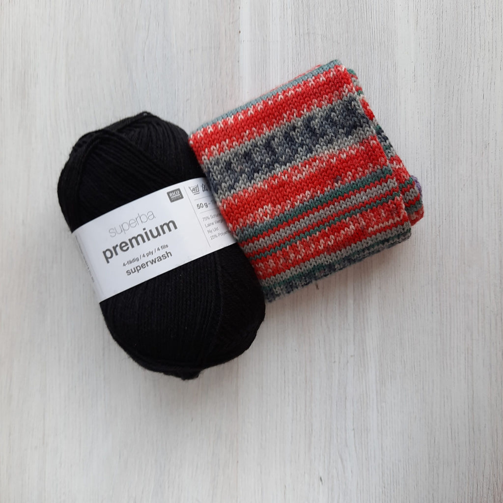 red, and greys nordic patterned striped sock tube and a black skein of yarn