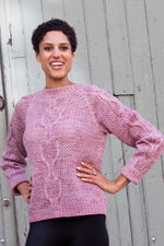a woman wearing a pink knit sweater with cables