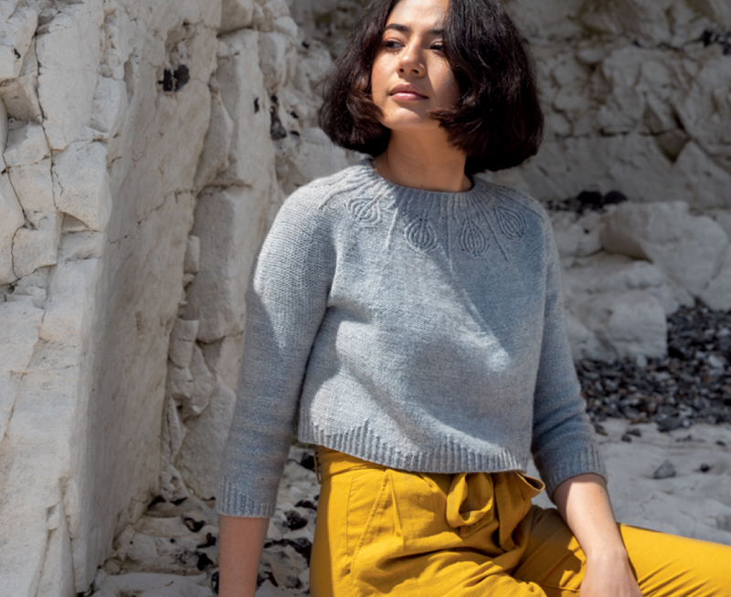 woman sitting by cliffs wearing a light grey knit sweater with a patterned yoke