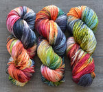 pink, grey,orange, green, red, and cream variegated skeins of yarn