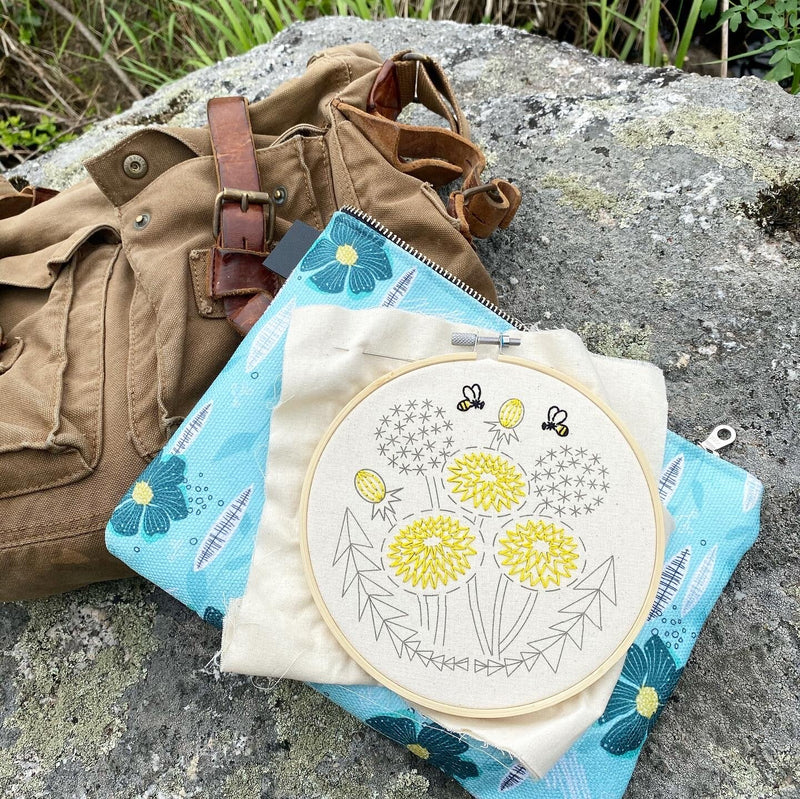embroidery kit with a duffel bag on a rock