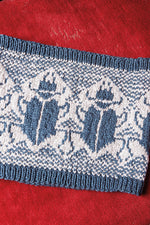 cowl in cream with ribbing and intarsia of beetles in medium blue