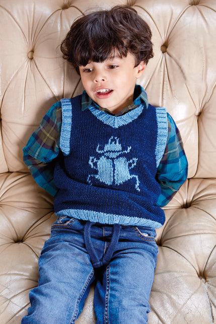 boy wearing a knit vest in dark blue with light blue ribbing and intarisa of a beetle.