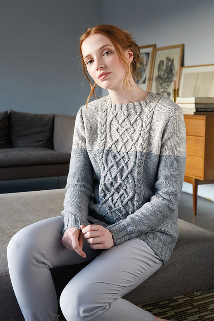 woman wearing a light and medium grey colour blocked knit sweater with cables on front body