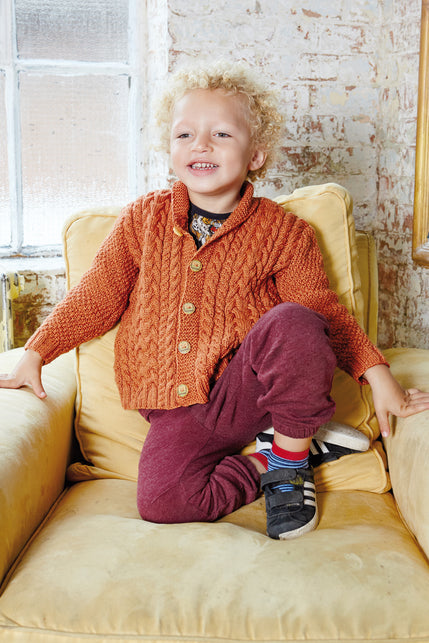 boy wearing a knit cabled orange cardigan