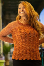 a woman wearing a burnt orange knit lace sweater
